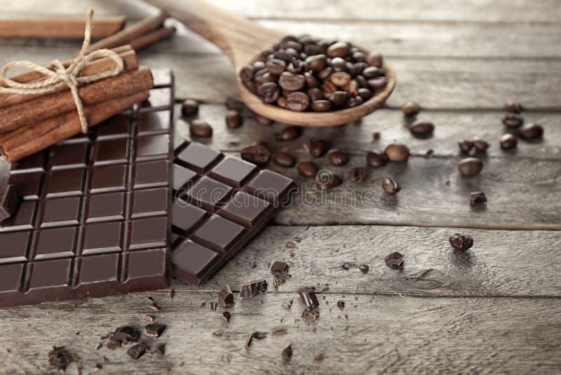 Вкусные шоколад, ручки циннамона и ложка с кофейными зернами на деревянном столе стоковые изображения
