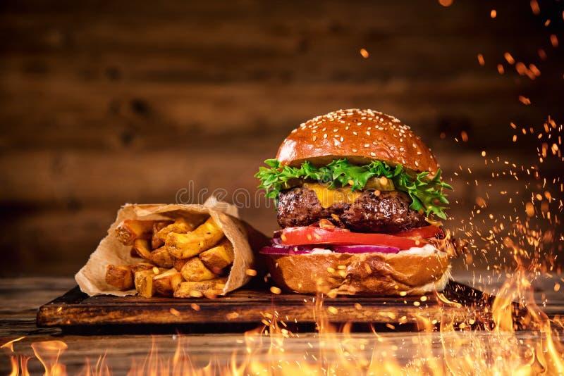 Вкусный бургер с французскими картофелем фри и огнем стоковое фото