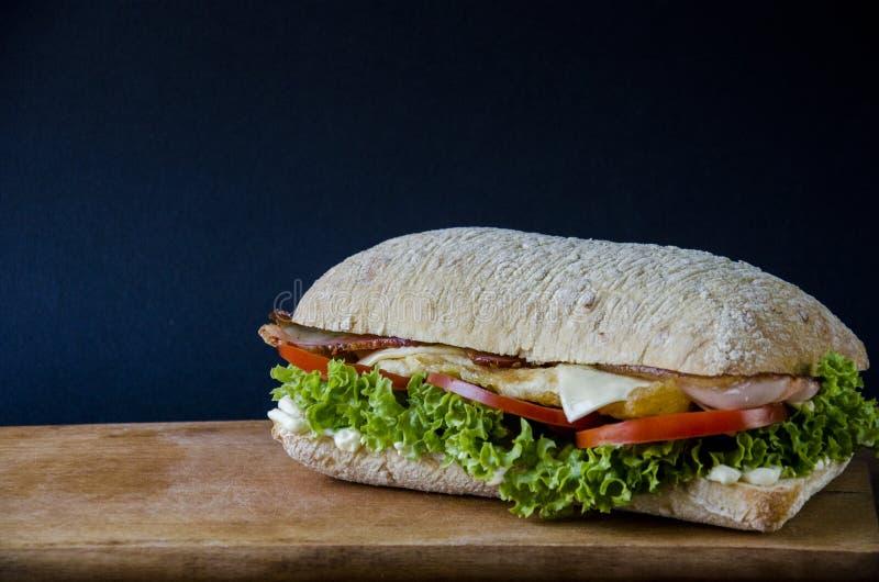 Вкусный бургер panini с беконом, сыром, салатом и мясом цыпленка на деревянной платформе на предпосылке голубой бумаги вкусно стоковые изображения