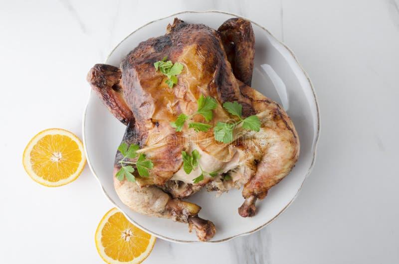 Вкусный горячий жареный цыпленок с апельсинами на большой плите на таблице wite мраморной, взгляде сверху стоковые фото