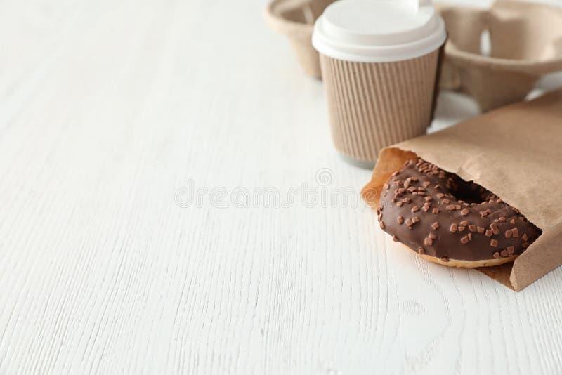 Вкусный донут в бумажном мешке и кофе на деревянном столе стоковые фото