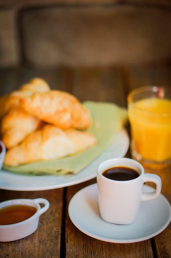 Вкусный завтрак: кофе с круассанами, апельсиновым соком и вареньем на w стоковое изображение