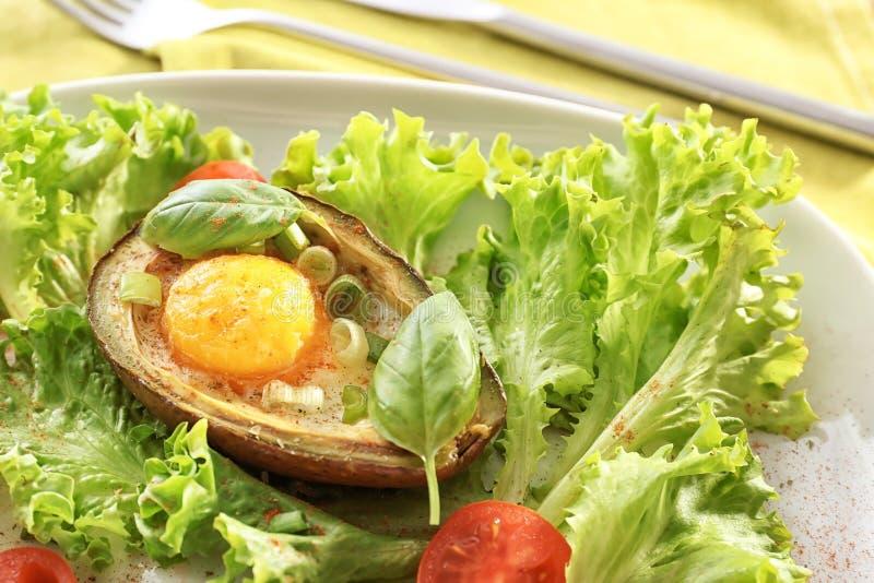 Вкусный испеченный авокадо с яйцом и свежими овощами на плите, крупном плане стоковые фотографии rf