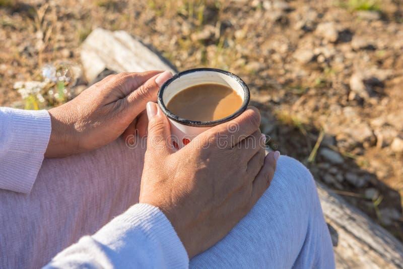 Вкусный кофе уничтоженный с наслаждением в природе взрослой женщиной стоковая фотография rf