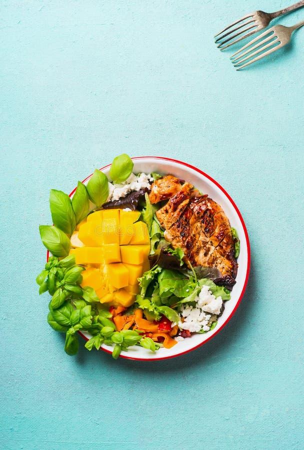 Вкусный салат с зажаренными в духовке отрезанными куриной грудкой и манго в шаре с столовым прибором на свете - голубой предпосыл стоковая фотография