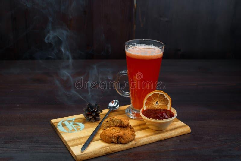 Вкусный сладкий горячий красный приправленный чай с вареньем клубники и печеньями овсяной каши стоит на деревянной винтажной табл стоковое фото