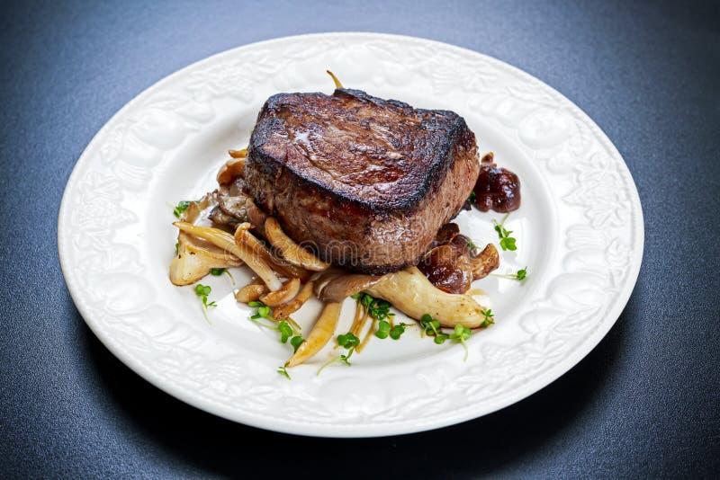 Вкусный стейк Mignon говядины с грибами и травами на плите стоковое изображение