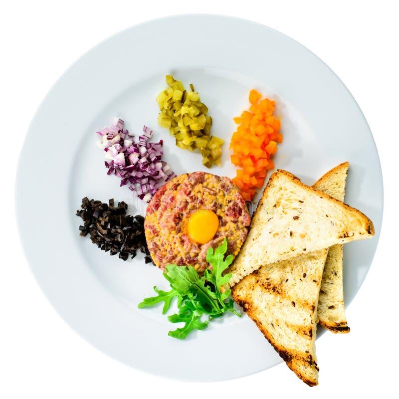 Вкусный тартар из говядины с яичным желтком, гренками и салатом в белизне стоковое фото rf