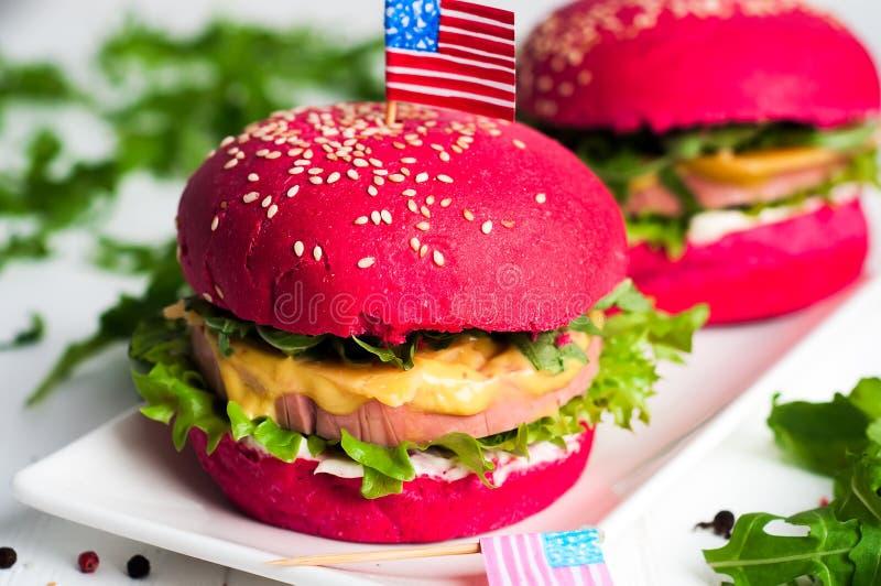 2 вкусных гамбургера с маленькими американскими флагами стоковое изображение