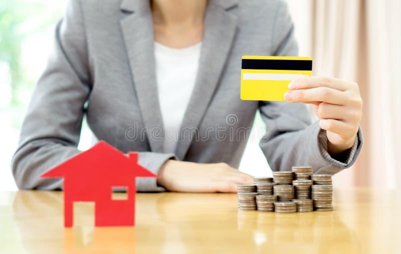 Вклад недвижимости кредитной карточкой Дом и монетки на таблице стоковые изображения