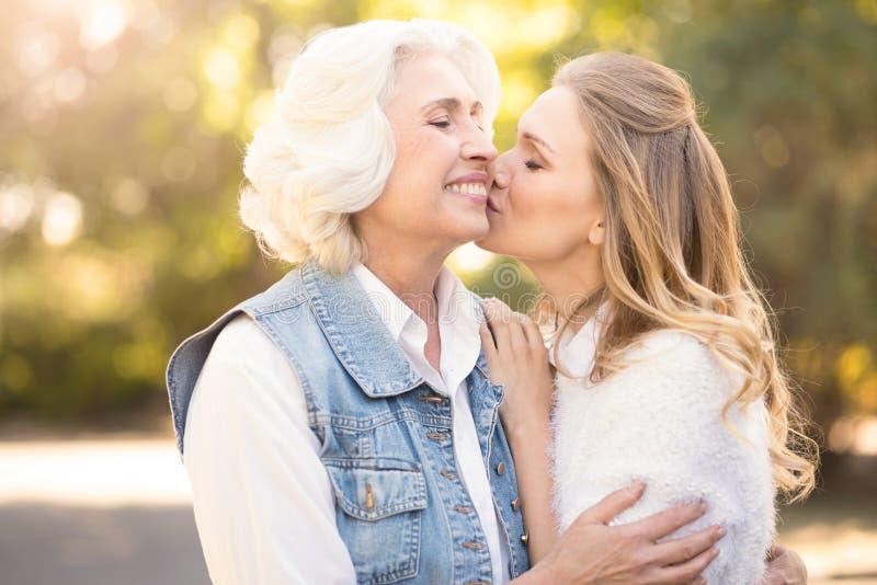 Включенная женщина целуя пожилую мать в парке стоковые изображения rf