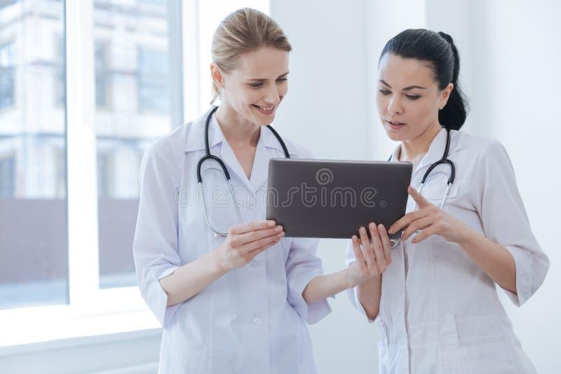 Включенные доктора используя цифровой прибор на больнице стоковые фото