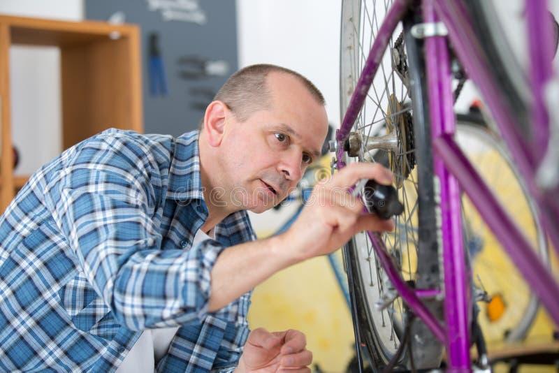 Владелец бизнеса ремонтируя велосипед стоковые изображения rf