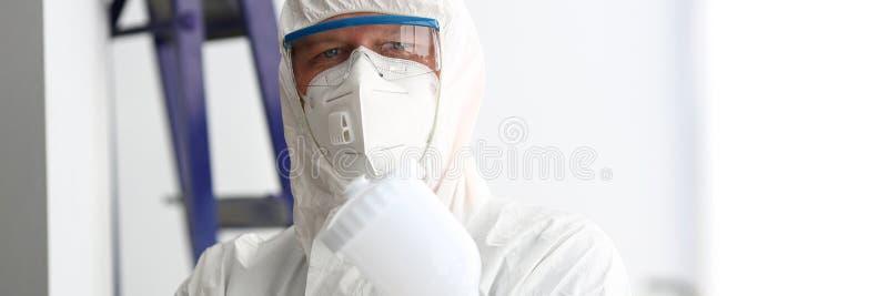 Владение рабочего класса в руке распыляет оружие нося защитный костюм стоковая фотография