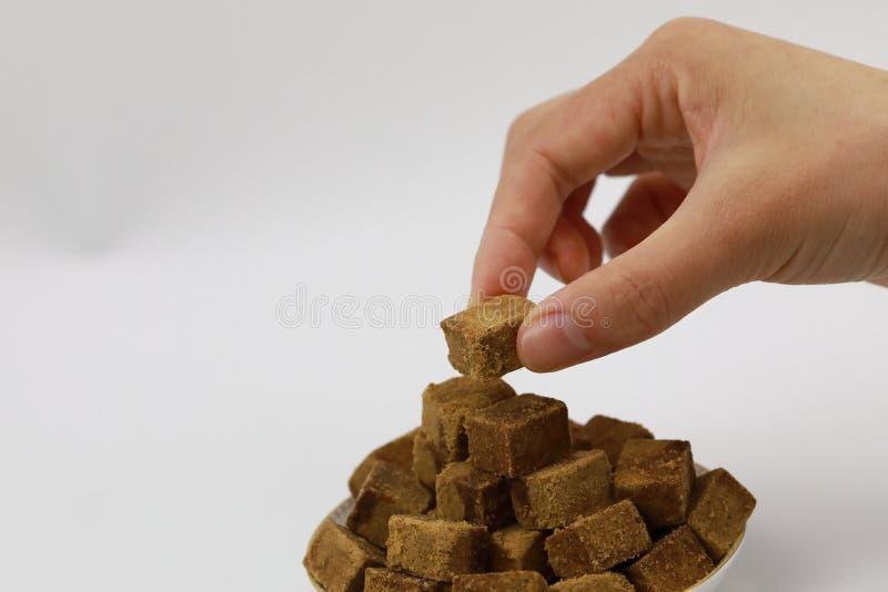 Владение руки женщины часть желтого сахарного песка, кубов трясет сахар на плите, на белой предпосылке, диабет стоковое изображение rf
