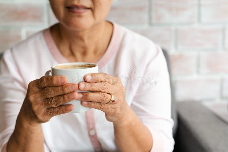 Владение старухи чашка горячего напитка кофе дома стоковые фотографии rf