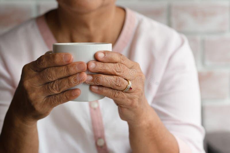 Владение старухи чашка горячего напитка кофе дома стоковая фотография