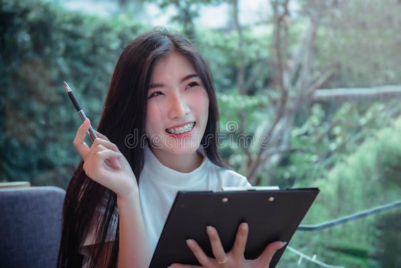Владение стиля дела азиатской девушки ручка и усмехаясь вещь эмоции положительная дня стоковое фото rf