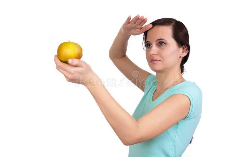 Владения одной девушки перед собой яблоко в руке стоковое изображение