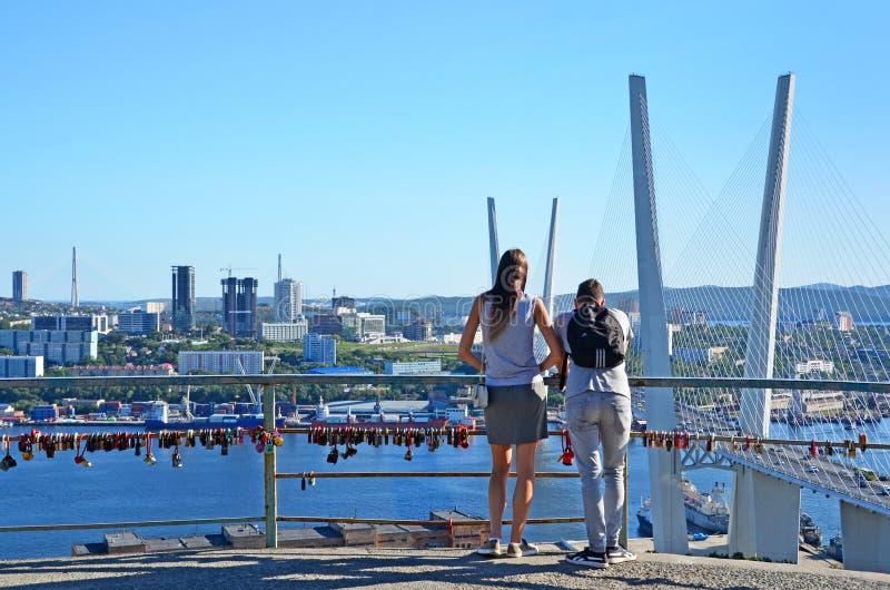 Владивосток, Россия, 31-ое августа 2017 Парень при девушка восхищая, который кабел-остали мост через залив Zolotoy Rog в Septem стоковая фотография rf