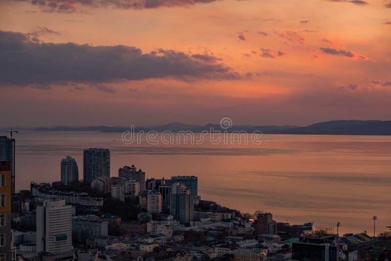 Владивосток, Россия - 7-ое апреля 2019: Панорамный вид города Владивостока против захода солнца стоковое фото rf