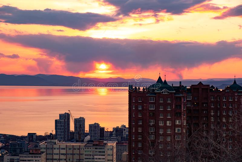 Владивосток, Россия - 7-ое апреля 2019: Панорамный вид города Владивостока против захода солнца стоковое изображение