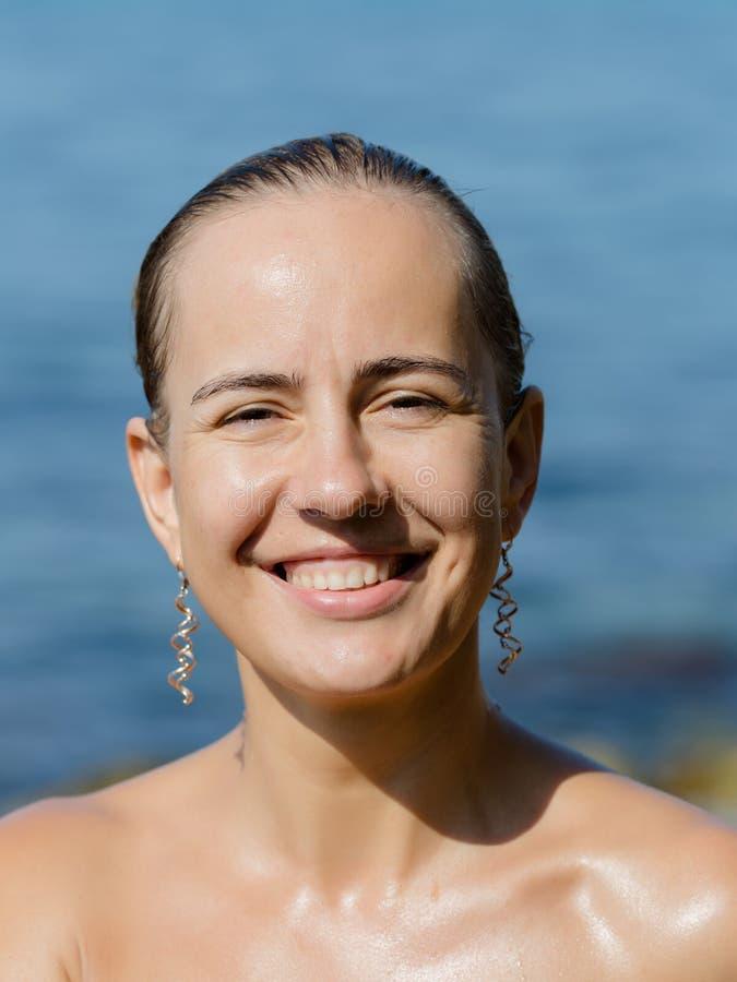 Влажная девушка представляет усмехаться и жмуриться от солнца стоковая фотография