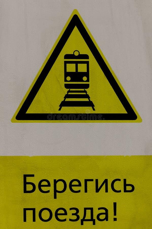 Влажный желтый предупредительный знак для поездов проходя рядом стоковые фото