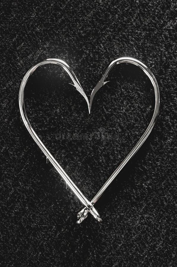 Влюбленность для удить концепцию: Удя крюки на форме сердца стоковые фото