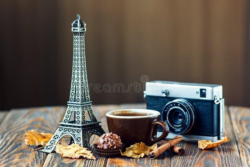 Влюбленность Париж! Подняли, винтажная камера, Эйфелева башня, кофейная чашка, шоколад и ручки циннамона на деревянной предпосылк стоковое фото rf