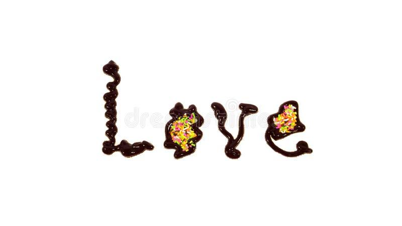 Влюбленность слова написанная шоколадом стоковые изображения rf