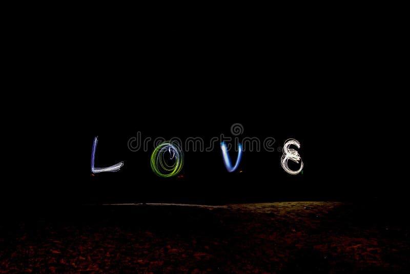 Влюбленность слова чертежа с светом сочинительства фейерверка стоковые изображения