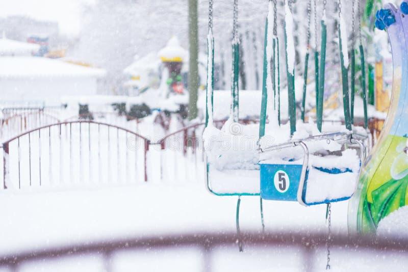 Внесезонная зима отказалась от парка пустого и предусматриванного в снеге Грустные фото спортивной площадки в зиме с carousel вни стоковая фотография rf