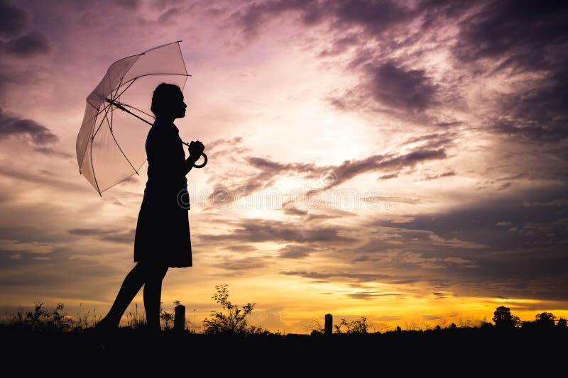 Внешнее и зонтик стиля силуэта тоскливости девушек идя одни в ее руке с облачными небесами и выравниваться стоковые фотографии rf