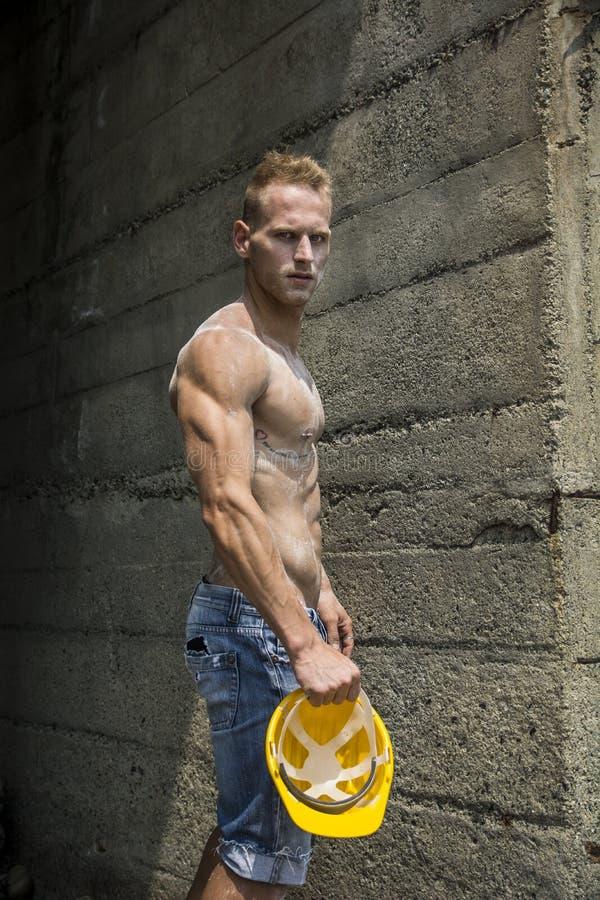 Внешнее красивого, мышечного молодого рабочий-строителя без рубашки стоковое изображение