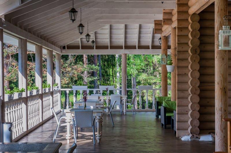 Внешнее патио с таблицами и вазами, деревенским домом в лесе стоковые фотографии rf
