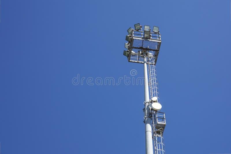 Внешние света и радиосвязь стадиона возвышаются против неба дневного времени голубого стоковое изображение