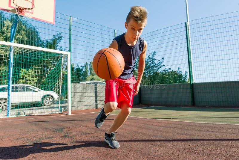 Внешний баскетболист улицы портрета играя с шариком на солнечный день стоковые изображения