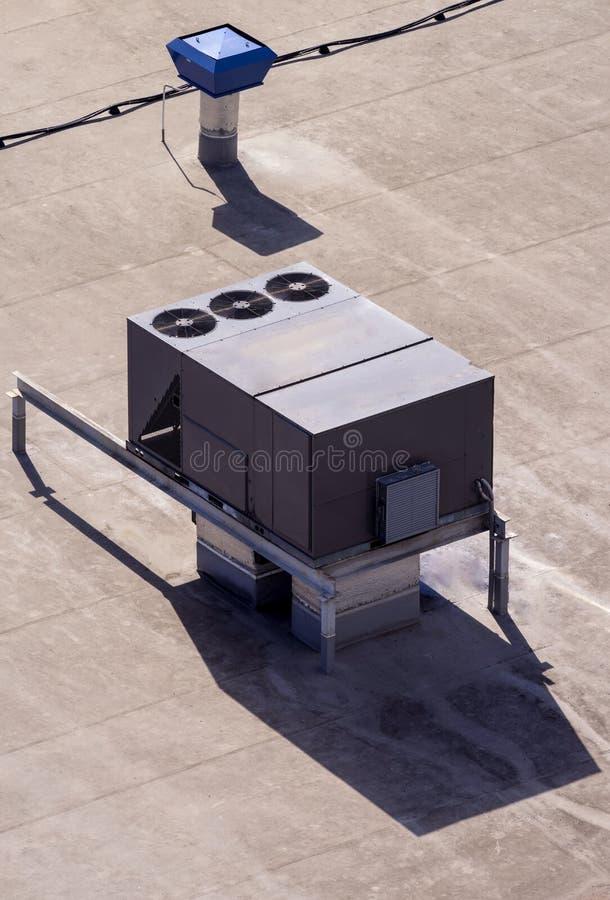 Внешний блок коммерчески кондиционера и системы вентиляции установлены на крышу промышленного здания стоковое изображение