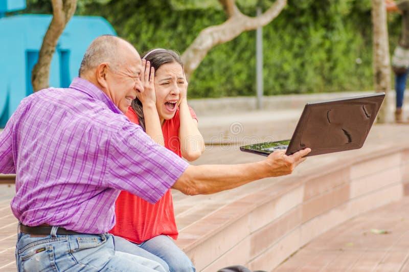 Внешний взгляд испуганного удерживания и компьютера и sacry daugher отца кричащее его хода папы компьютер в стоковое изображение rf