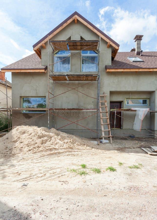 Внешний взгляд нового дома под конструкцией и картиной Леса для экстерьера штукатуря дома стоковое изображение