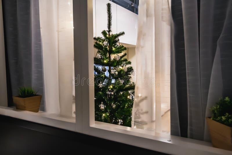 Внешний взгляд через окно с бежевыми и серыми занавесами яркая и уютная комната с елью рождества со стеклянными шариками и стоковое изображение rf