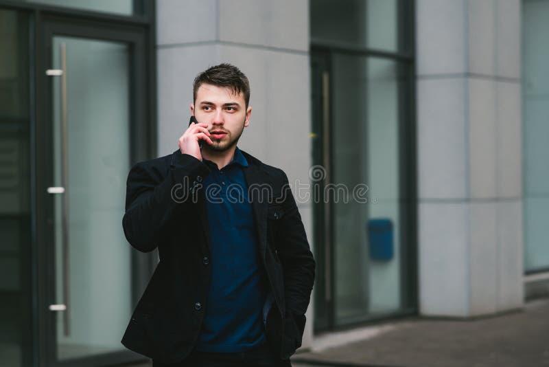 Внешний портрет бизнесмена хорошего человека усмехаясь говоря на телефоне на предпосылке современного городского ландшафта стоковые фото