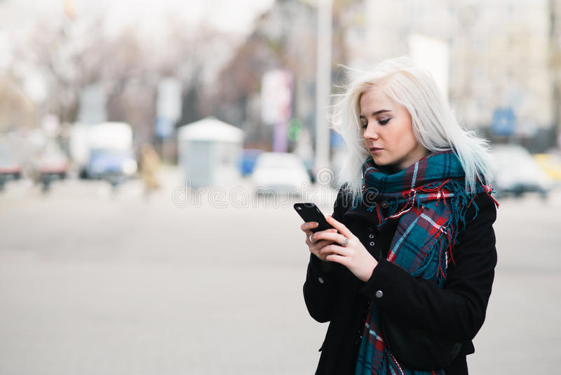Внешний портрет красивого белокурого платья девушки весной наслаждаясь серединой телефона города Прогулка вокруг города стоковое изображение
