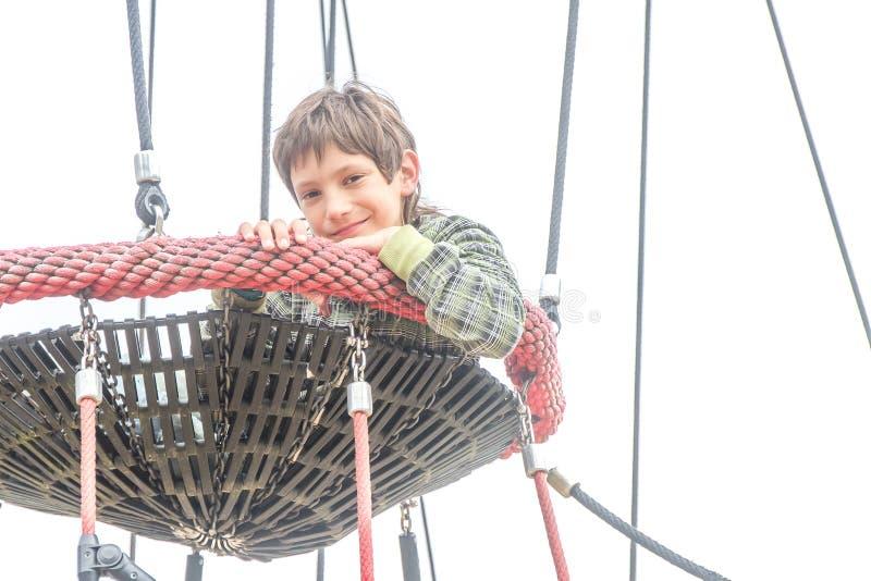 Внешний портрет мальчика ребенка наслаждаясь ее временем на спортивной площадке стоковые изображения
