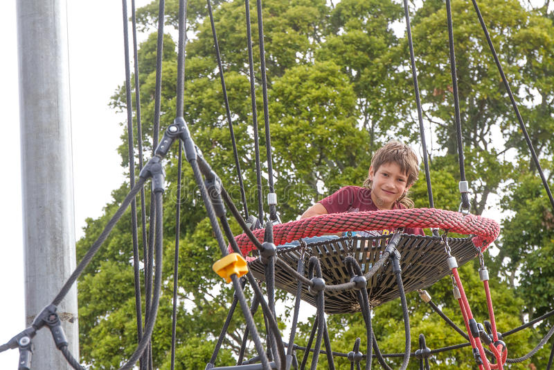 Внешний портрет мальчика ребенка наслаждаясь ее временем на спортивной площадке стоковое изображение