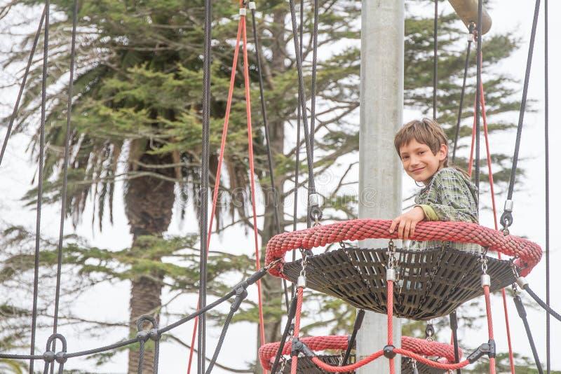 Внешний портрет мальчика ребенка наслаждаясь ее временем на спортивной площадке стоковое фото rf