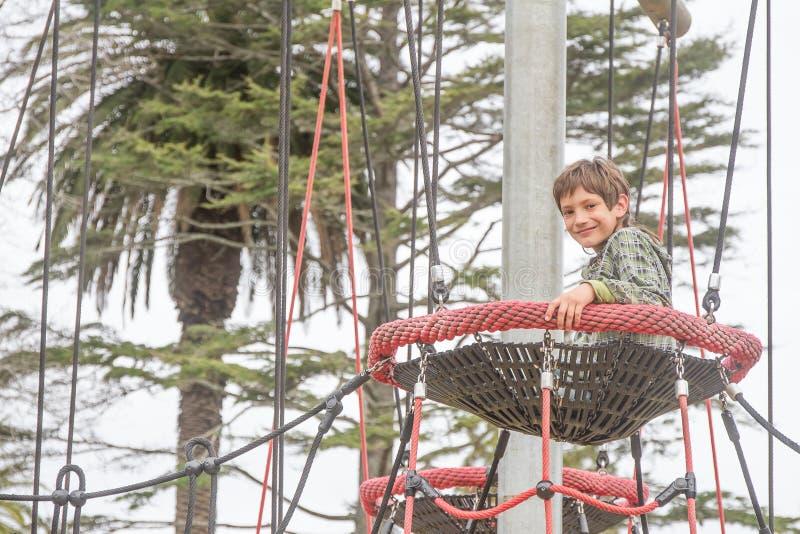 Внешний портрет мальчика ребенка наслаждаясь ее временем на спортивной площадке стоковые фото