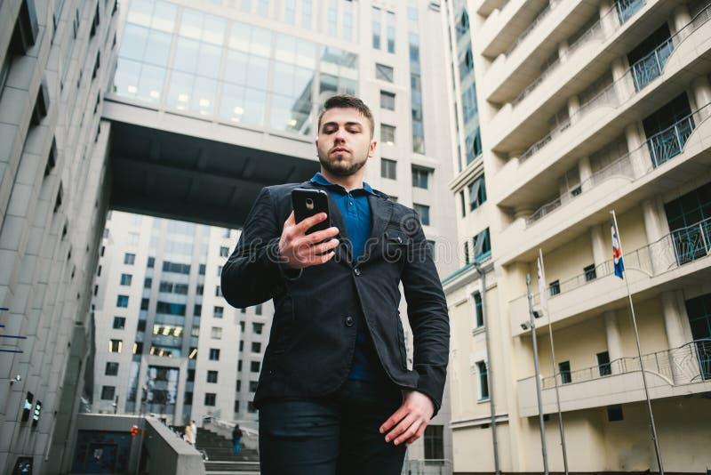 Внешний портрет молодого бизнесмена с бородой которая использует мобильный телефон на предпосылке современной архитектуры стоковое изображение