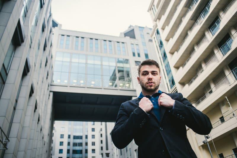 Внешний портрет молодого красивого бизнесмена в костюме который представляет против фона современного делового центра стоковое фото rf